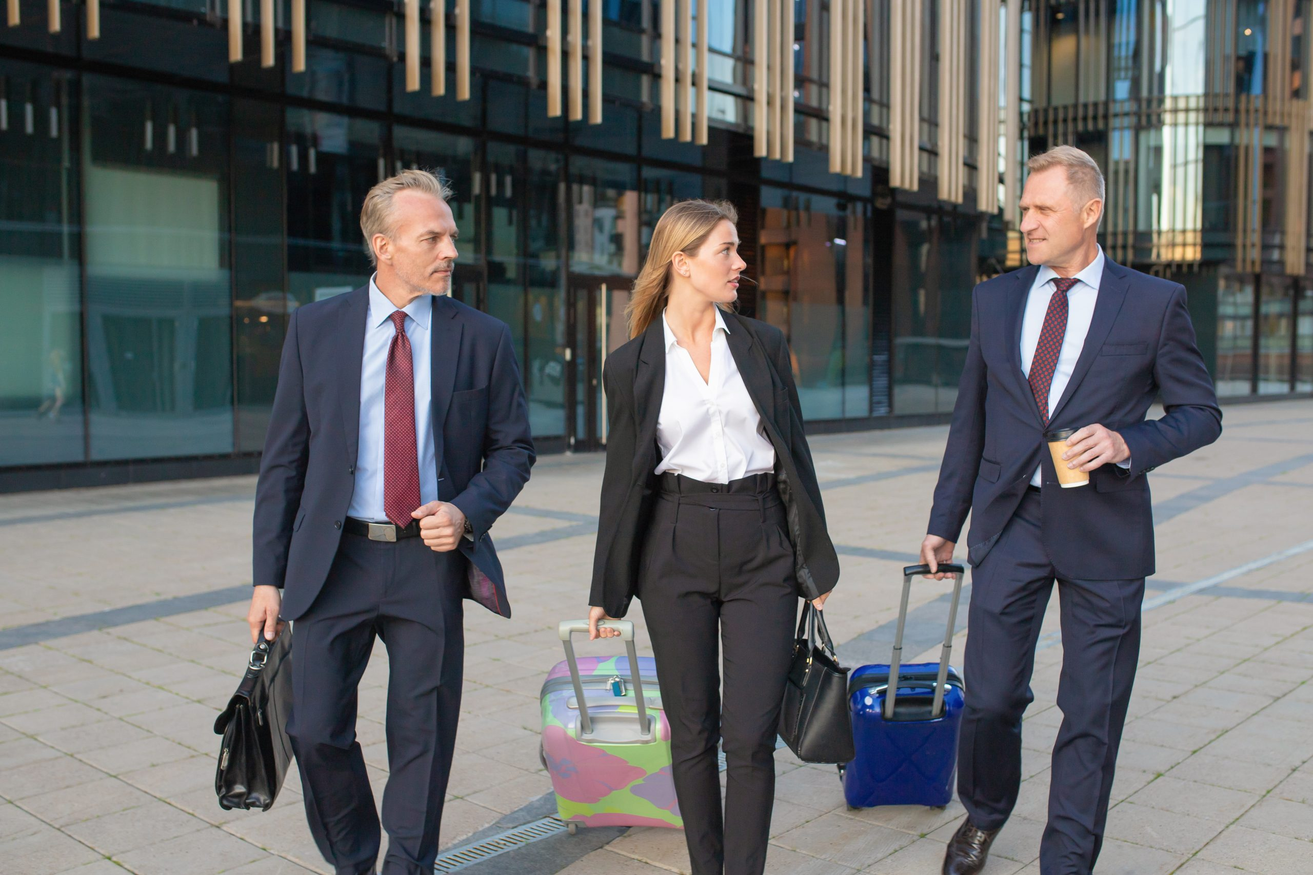 Confident businesspeople travelling with luggage, walking to hotel, wheeling suitcases, talking. Front view. Business trip or corporate communication concept